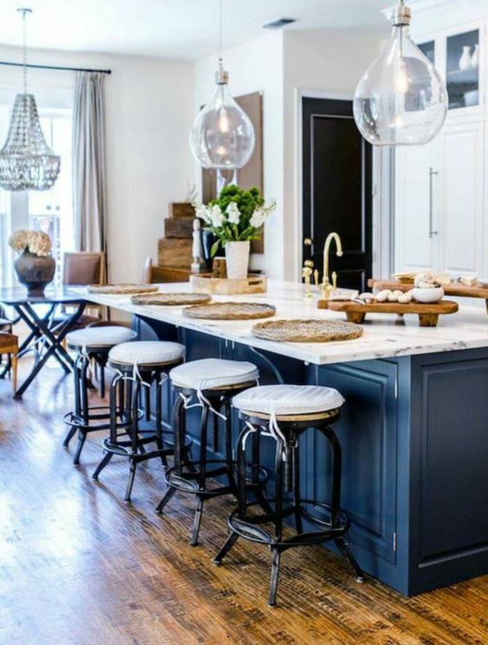 cuisine bleu canard, meuble bleu canard, deco bleu canard, luminaires en forme de boules en verre, quatre tabourets avec des coussinets blancs et pieds en métal noir, grand lustre brillant en cristaux, parquet en beige et taches noires