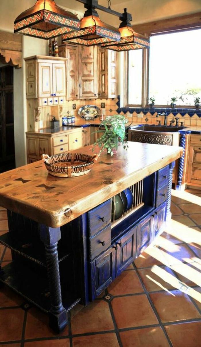 cuisine bleu, peinture bleu canard, trois luminaires en mosaïque colorée en rouge et jaune, îlot en bleu canard et plan en bois rude, style rustique