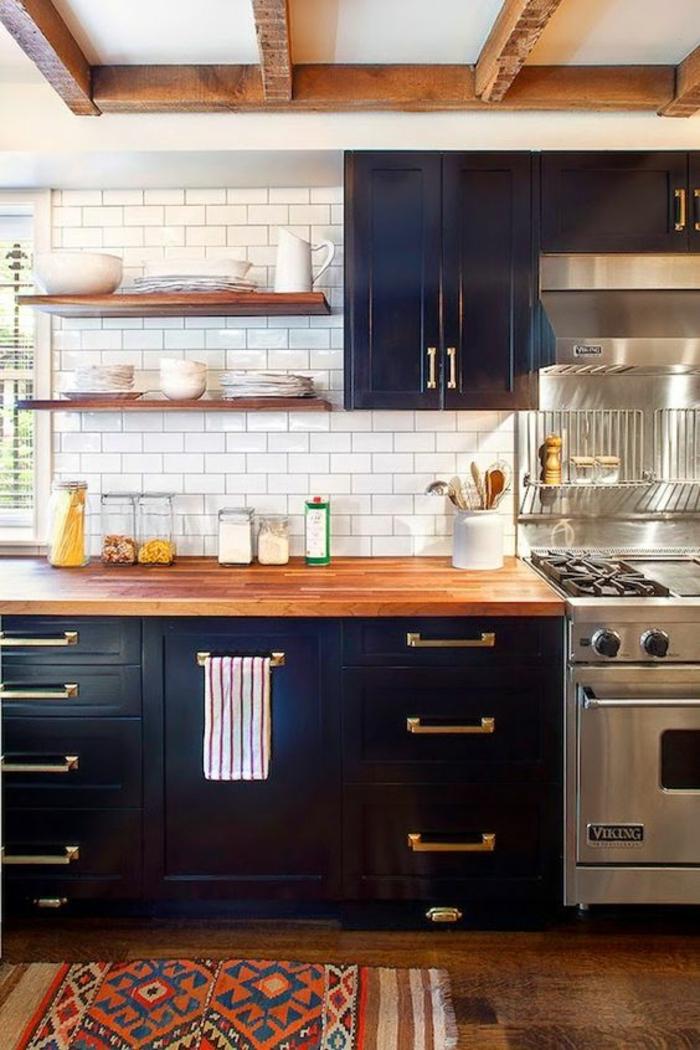 meuble bleu canard, cuisine en style rustique, avec des poutres en bois, mur en briques blanches, meuble avec plan de travail au bois laqué, tapis vintage au sol en orange et rouge, avec des franges blanches