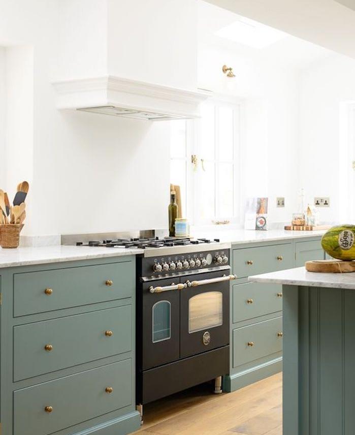 facade cuisine de couleur vert gris, teinte céladon, parquet clair, four gris anthracite, mur couleur blanche, boutons dorés