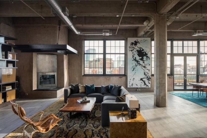 mobilier industriel, canapé d'angle en gris anthracite avec coussins décoratifs, table basse en bois sur tapis beige et noir
