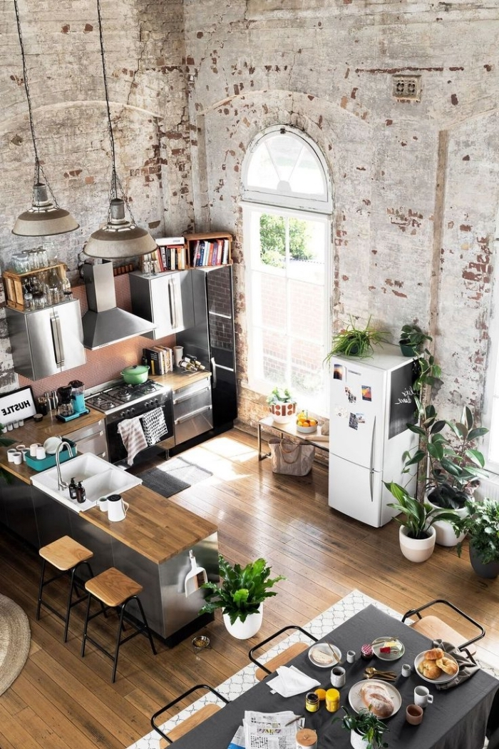 chaise industrielle, aménagement cuisine ouverte aux murs en briques et plancher en bois clair, cuisine d'angle avec armoires en gris métallique et comptoir en bois