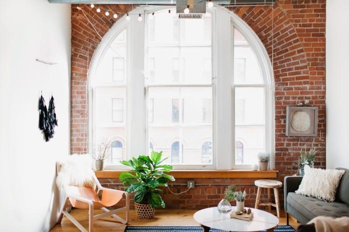 déco de salon loft industriel, canapé en velours gris avec coussin moelleux en blanc et petite table basse en blanc