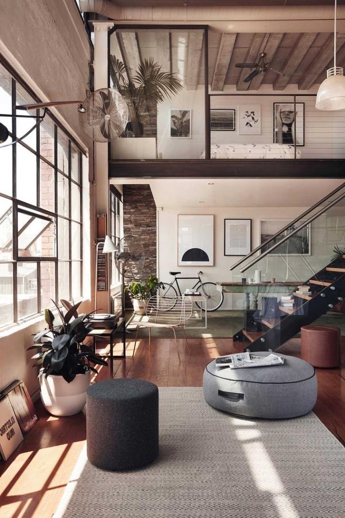 loft industriel, plafond avec ventilateur et tuyaux apparents, escalier moderne en bois et verre, revêtement de sol en bois