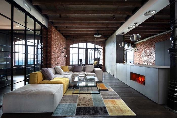 idee deco salon, canapé d'angle en gris et jaune avec coussins décoratifs, table rectangulaire en verre avec pieds noirs