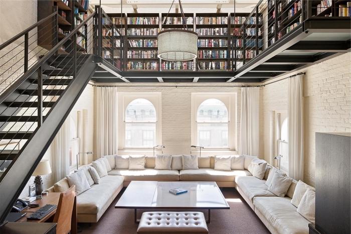 aménagement studio loft aux murs briques blanches avec escalier noir, suspension luminaire en bois et blanc