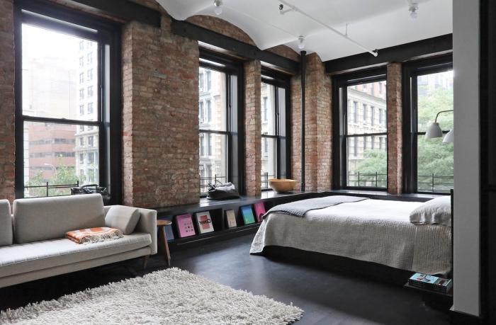 déco de chambre à coucher à design loft industriel aux murs briques et plafond blanc, tapis moelleux blanc sur plancher noir
