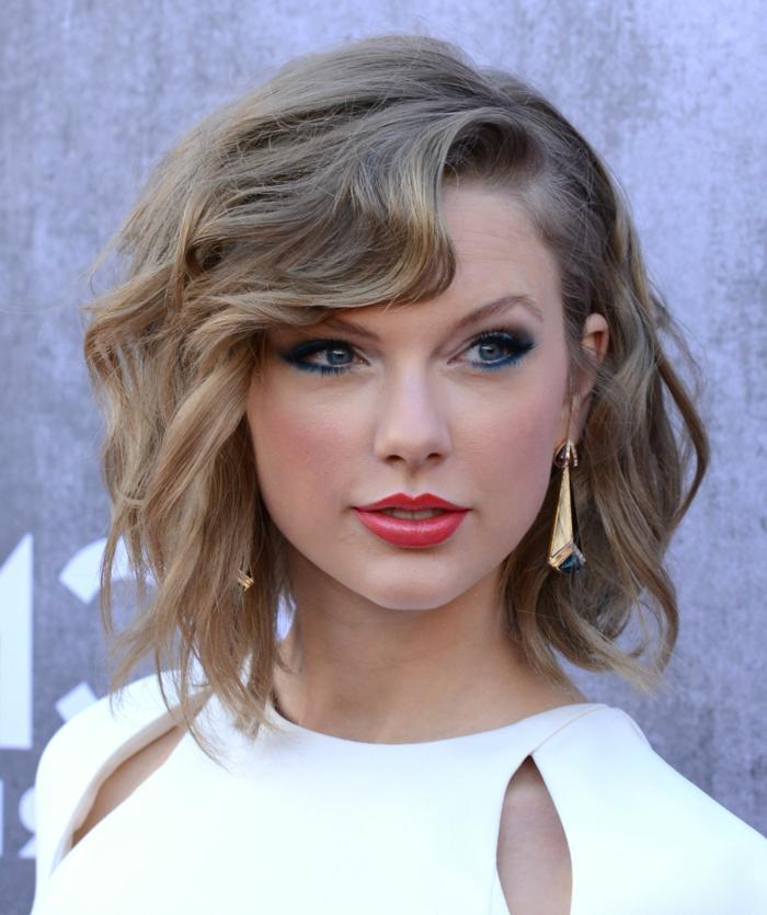 coupe courte cheveux frisés eyeliner bleu, rouge à lèvres orange, boucles d'oreilles pendantes
