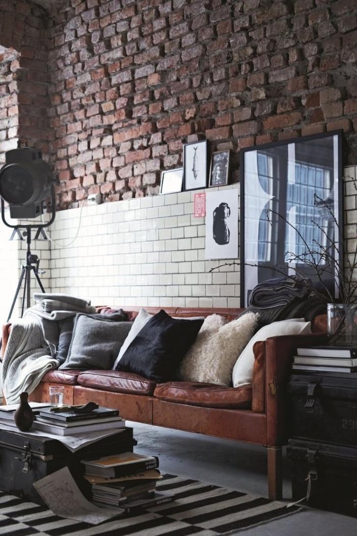 déco loft industriel de salon aux murs briques et plancher en béton, collection de livre et coffre noir
