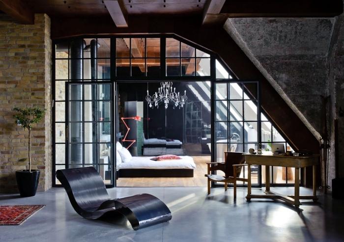 idee deco salon, chambre à coucher avec lit bas et lustre en cristaux, salon aux murs briques et plafond bois foncé