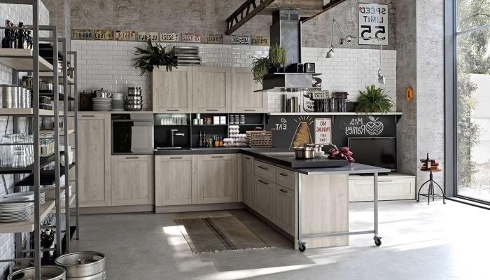 aménagement de cuisine loft industrielle, meubles de cuisine en bois clair avec comptoir noir et plancher en béton