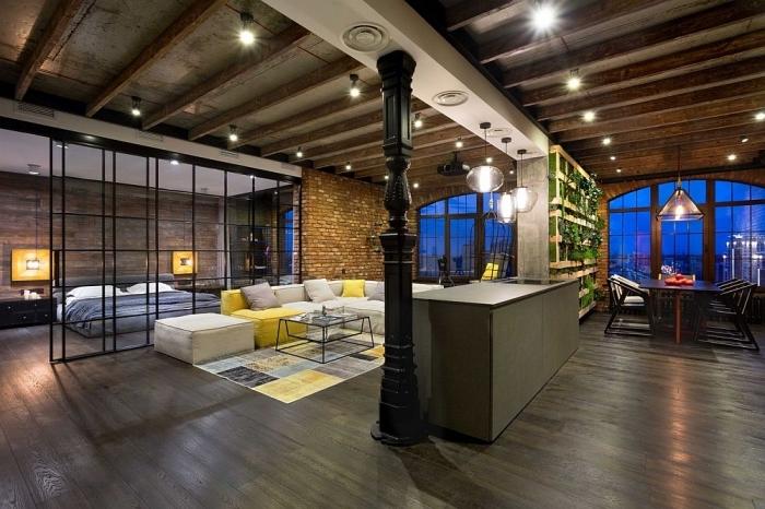 aménagement de studio loft industriel aux murs briques et plafond avec poutres en bois, éclairage corde électrique avec ampoules