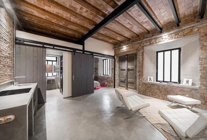 déco style loft industriel avec plancher en béton et plafond en briques et poutres bois, meubles de salon en blanc