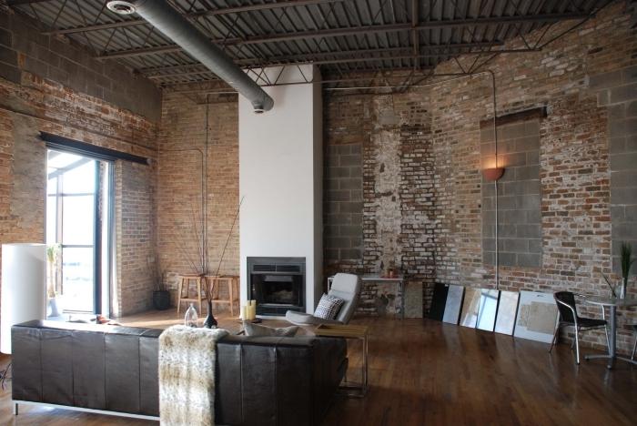 déco de loft aux murs briques et plancher en bois, canapé en cuir marron avec chaise grise et petite table en bois