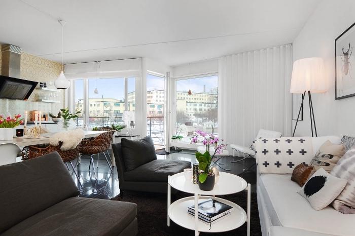 meuble scandinave, papier peint beige à motifs volutes, peinture blanc et noir dans cadre photo noir