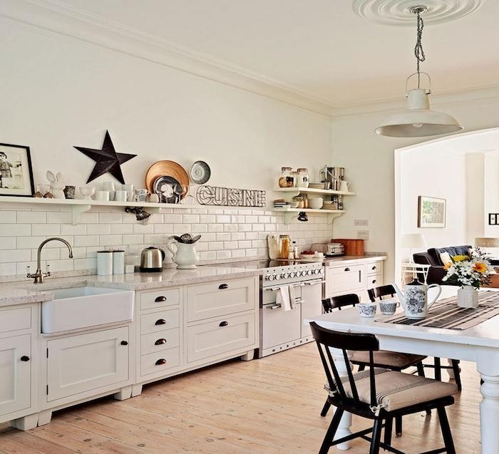 cuisine americaine avec façade blanche et carrege blanc, etageres ouvertes rangement vaisselle vintage, parquet clair, table et chaises en bois, canapé gris