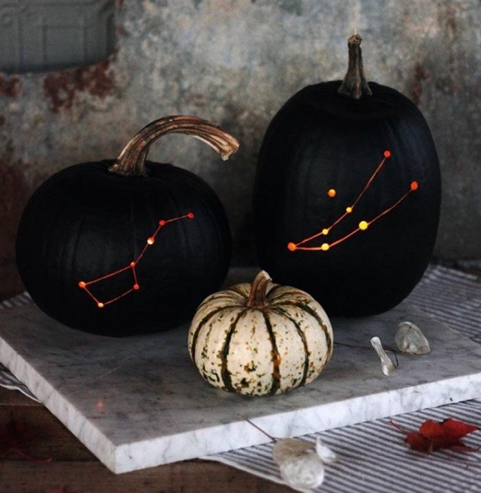 activité manuelle halloween, grandes citrouilles peintes noires avec constellations lumineuses