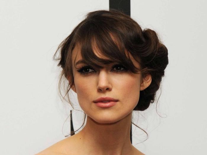 coiffure célébrité Keira Knightley, cheveux attachés en chignon décontracté avec mèches devant et frange de côté