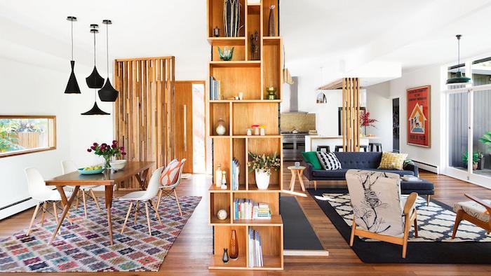 modele de cuisine americaine blanche ouverte sur un salon avec canapé gris et chaises en ois et tissu, parquet marron, bibliotheque en guise de separation d'une salle à manger avec table en bois et chaises scandinaves