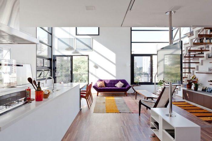 modele de cuisine americaine blanche ouverte sur salle à manger avec table blanche et chaises en bois, tapis à rayures et canapé violet, escalier en bois