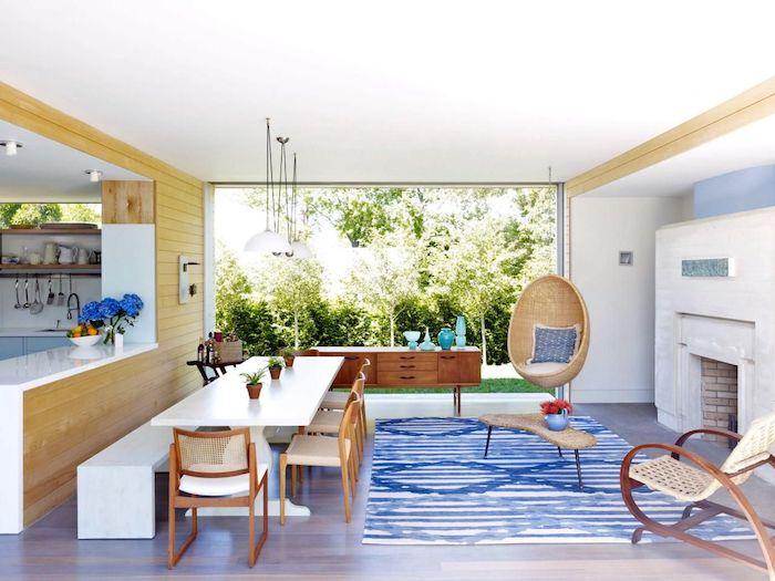 cuisine ouverte sur salon, modele de cuisine semi ouverte, mur bar en bois, table et banc blancs, chaises en bois, cheminée blanche, balançoire en rotin, grande fenetre qui donne sur un jardin vert