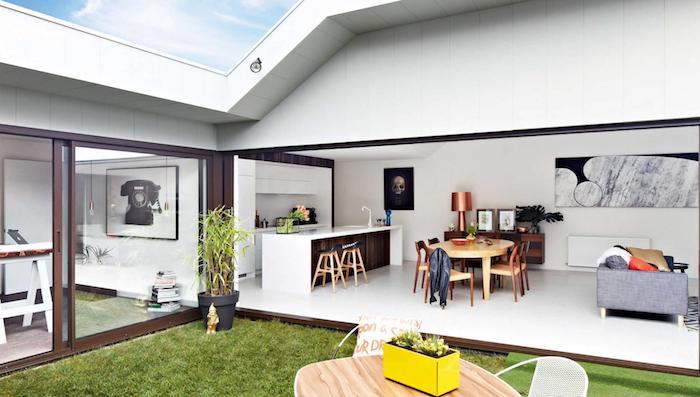 exemple de cuisine avec bar bois avec plan de travail blanc, ouverture sur salle à manger en table et chaises en bois, salon avec canapé gris, espace qui donne sur un jardin