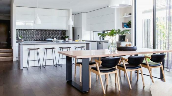aménagement cuisine ouverte blanche avec bar blanc et crédence noire, salle à manger avec table en bois et metal et chaises en bois et cuir noir, parquet marron