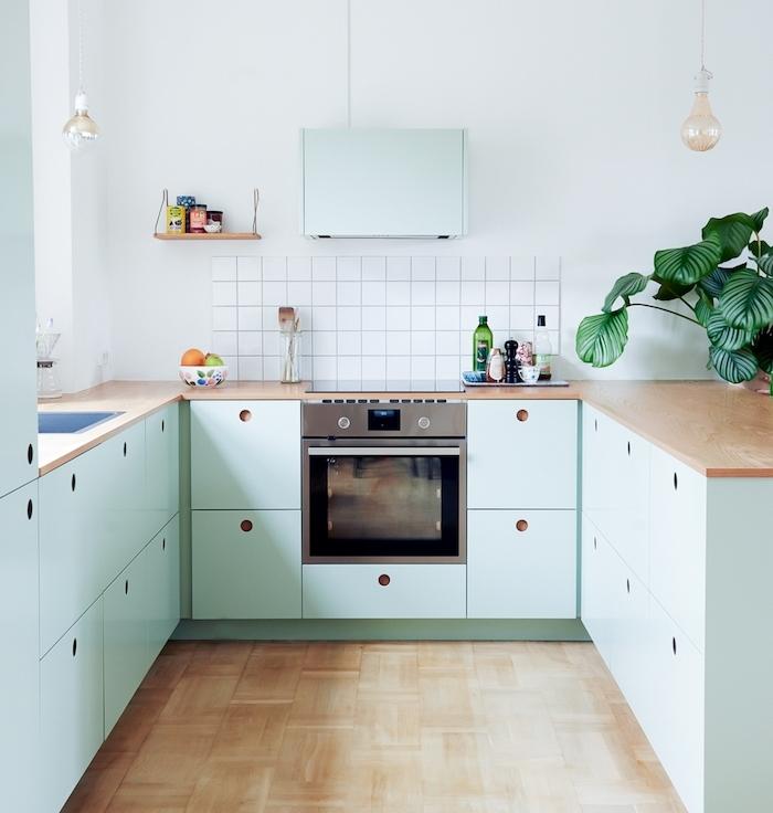 cuisine campagnarde en bleu clair, parquet bois clair, credence carrelage blanc, plan de travail bois, suspensions ampoules cuivrées, plante verte