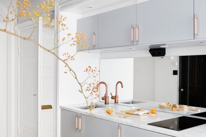 decoration scandinave, cuisine moderne aux meubles gris clair et comptoir en marbre avec évier cuivré