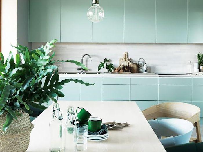 idee de facade cuisine bleu celadon, crédence grise, plan de travail en marbre, table blanc cassé, chaises beige, bleu et vert, feuilles de plantes vertes dans un panier