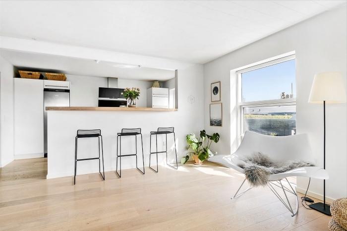 decoration scandinave, plafond et murs blancs avec plancher en bois stratifié, cuisine avec ilot centrale blanc et comptoir en bois