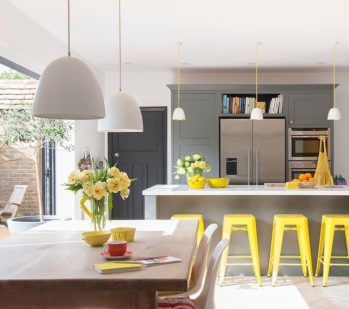 petite cuisine ouverte en gris avec bar gris et tabourets jaunes metalliques, ouverture sur salle à manger en table bois et chaises scandinaves