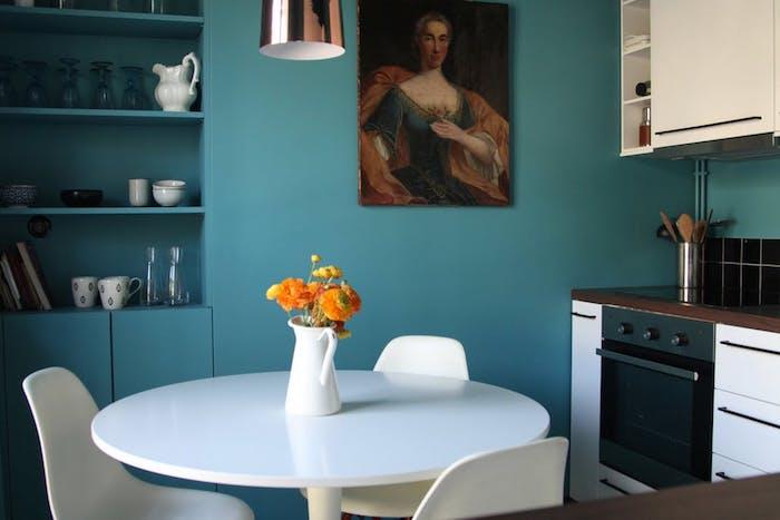 modele de cuisine ouverte sur salle à manger, façade, table et chaises blanches, mur peinture bleu pétrole