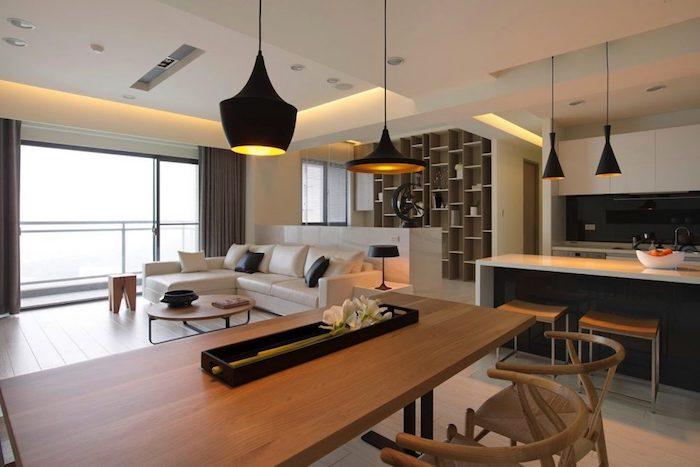 exemple de cuisine ouverte en noir et blanc, salle à manger avec table et chaises en bois, canapé blanc et table basse en bois, suspensions noires