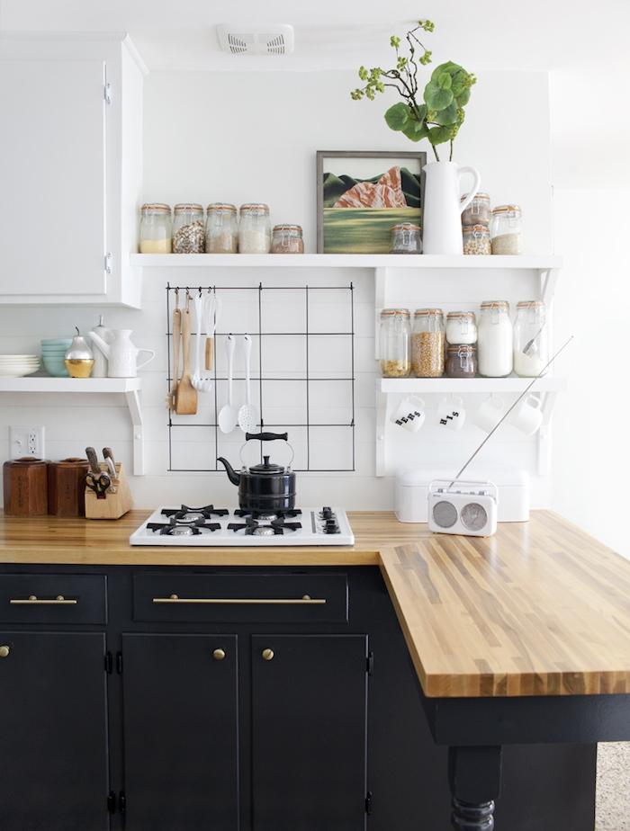 cuisine rénovée avec facade repeinte en noire à poignées et boutons dorés, plan de travail bois, mur et meuble hait cuisine blanc, etagere rangement pots d ingredients