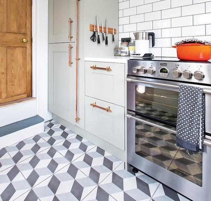 modele de cuisine rénovée, meuble cuisine repeint en gris perle, poignées placards en tube de cuivre, fourneau inox, carrelage credence blanc, carrelage sol motifs géometriques gris et blanc