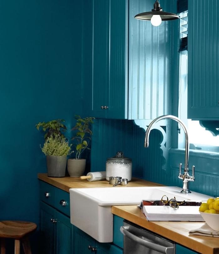 modele de cuisine ancienne campagne couleur bleu canard avec plan de travail bois, évier blanc, pots d herbes aromatiques, lavabo blanc et robinetterie argent
