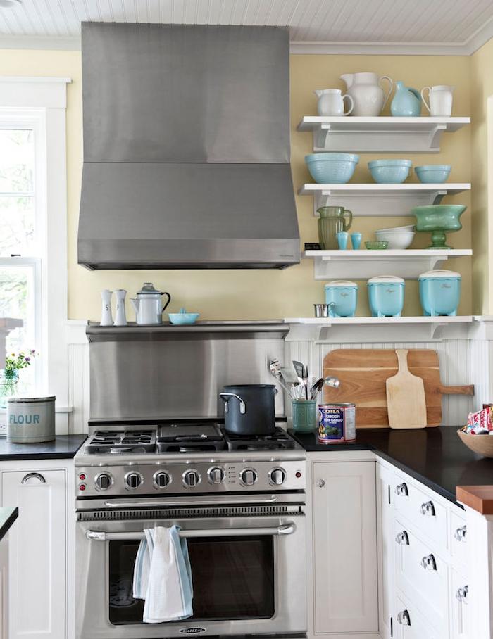 cuisine rénovée, repeinte en blanc et mur jaune, electromenager inox, plan de travail noir, planches a decouper bois, vaisselle bleu et blanc sur etageres blanches