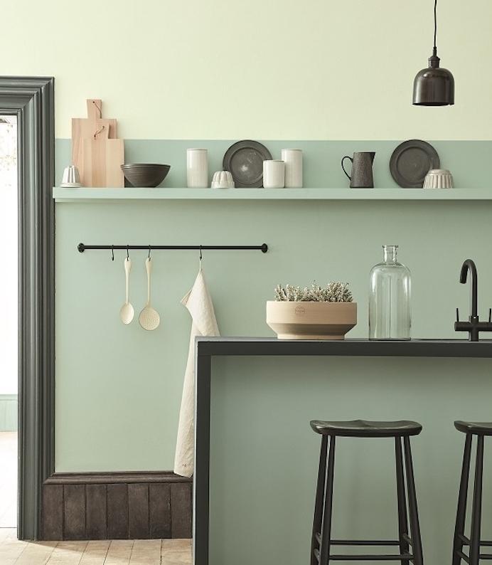 ameangement cuisine couleur vert celadon, avec des touches de noir et blanc, tabourets et bar avec plan de travail noir, vaisselle noire et blanche, parquet en bois brut