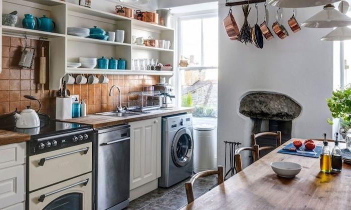 amenagement cuisine rustique avec credence carrelage marron, electromenager inox, etageres ouvertes blanches avec vaisselle bleue, blanche et cuivre, sol carrelage gris, table et chaises en bois