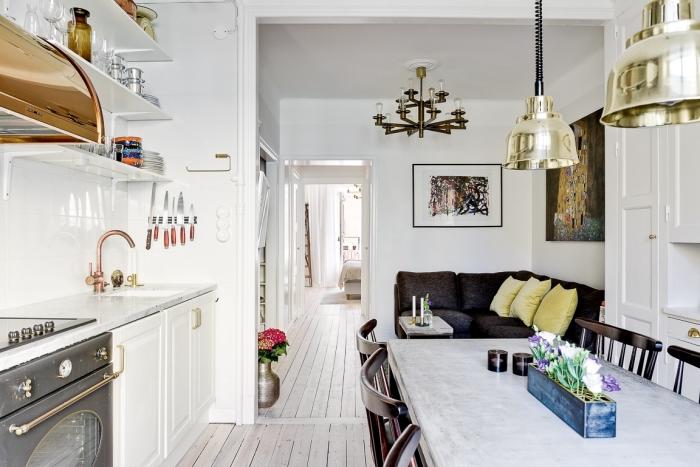 deco nordique, canapé d'angle en noir avec coussins jaune pastel, cuisine ouverte vers le salon avec salle à manger