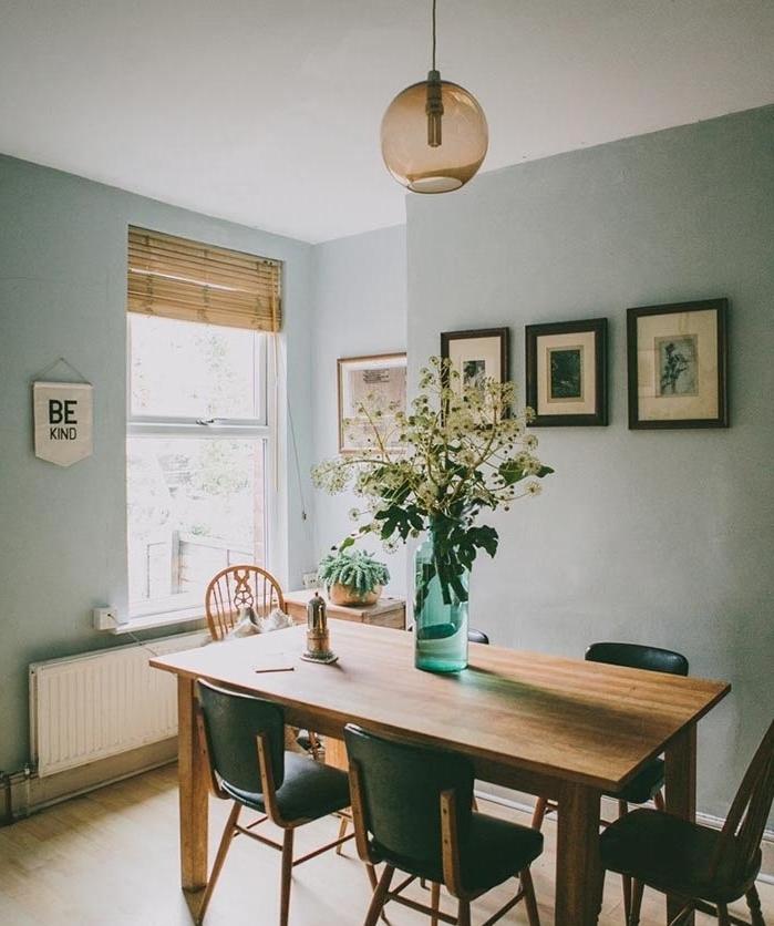 idee amengamenet salle à manger aux murs peinture vert de gris, nuance céladon, table et bois et chaises noires, suspension boule, parquet clair