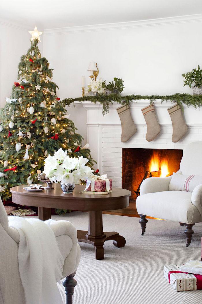 modele de sapin décoré de guirlande lumineuse et ornements rouges et blancs, près d une cheminée romantique, table basse en bois, fauteuils blanc cassé