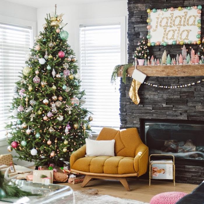 modele de sapin décoré de guirlande lumineuse et boules de noel de couleurs diverses, jaune, bleu, argent, rose, rouge, or près d une cheminée en pierre et fauteuil jaune moutarde