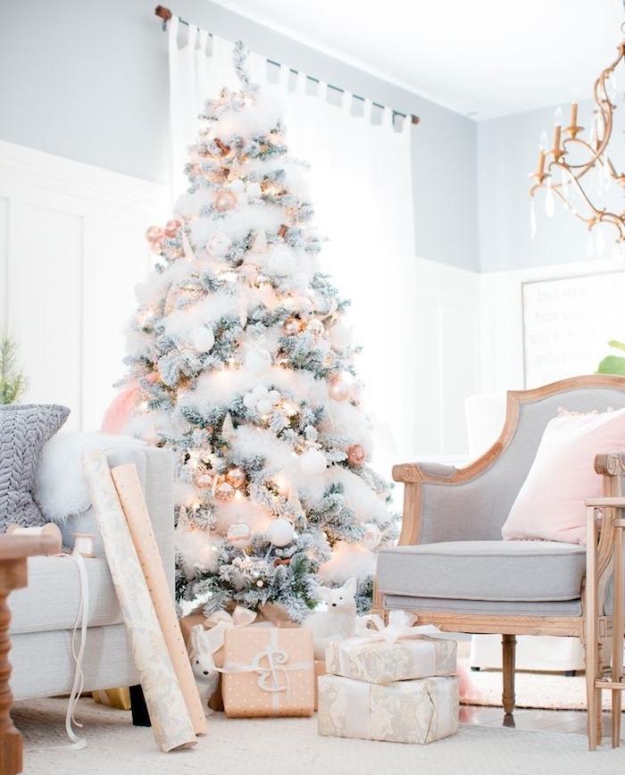 sapin de noel decoration de guirlandes blanches et boules de noel dorées, chaise grise, paquets cadeaux beige et gris, lustre élégant
