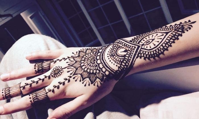 tatouage au henné noir sur la main, dessin ethnique pour femme, tattoo non permanent à design florale