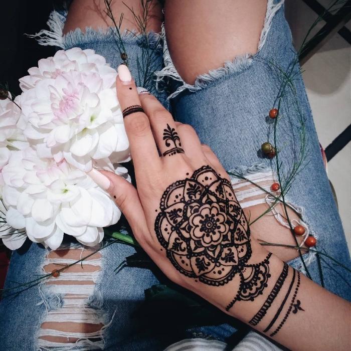 henné noir, manucure aux ongles longs et vernis blancs, modèle de tatouage au henné sur le doigt et la main