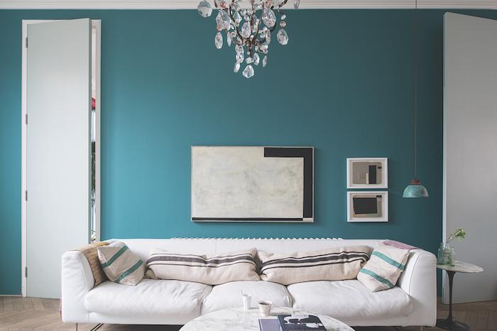 modele de salon bleu petrole, mur repeint en bleu de tonalité pastel, canapé blanc, décoré de coussins beife à rayures vertes et marron, table basse en marbre, lustre élégant