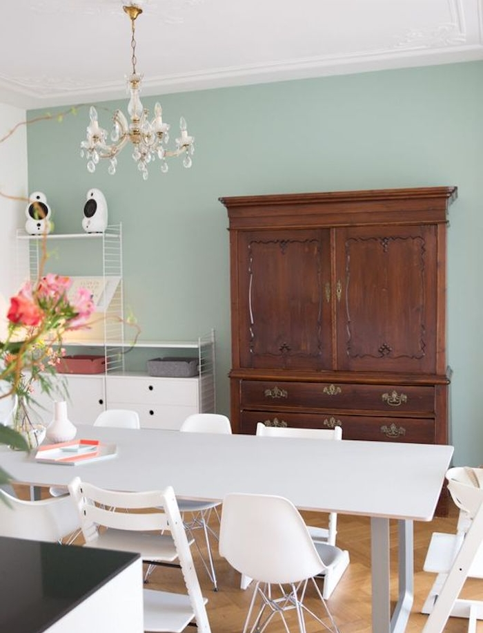 deco salle a manger avec murs couleur vert céladon clair, table et chaises salle à manger style scandinave, armoire en bois vintage, lustre élégant
