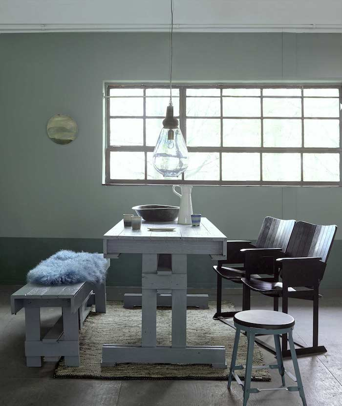 mur couleur vert de gris, table et banc blanc, chaises noires assemblées en banc, parquet en bois usé, suspension originale